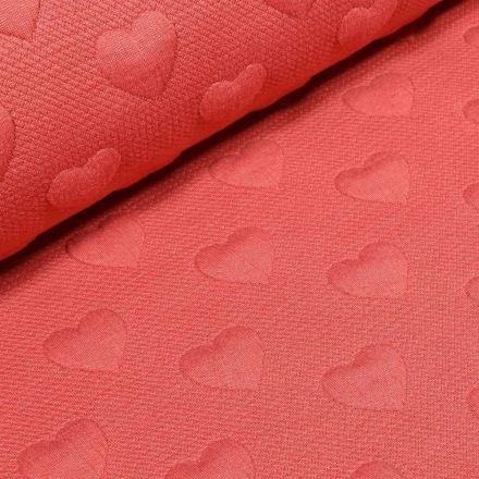 Tissu Sweat Cœurs en relief sur fond Corail - Par 10 cm