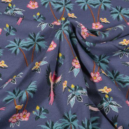 Tissu Jersey Coton Palmiers fleurs d'hibiscus et perroquet sur fond Bleu denim