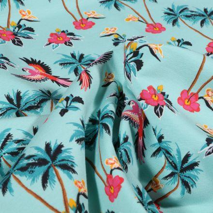 Tissu Jersey Coton Palmiers fleurs d'hibiscus et perroquet sur fond Bleu lagon