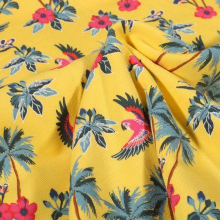 Tissu Jersey Coton Palmiers fleurs d'hibiscus et perroquet sur fond Jaune