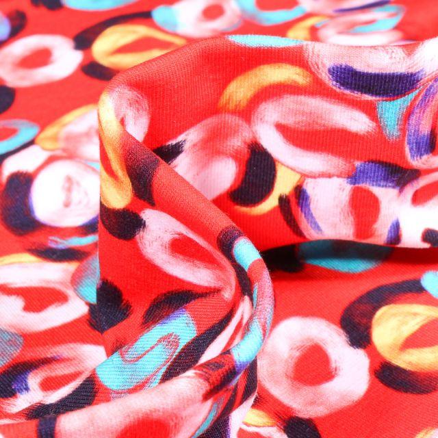 Tissu Jersey Coton Formes abstraites multicolores sur fond Rouge