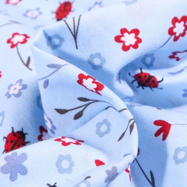Tissu Coton imprimé Ladybug Coccinelle et fleurs sur fond Bleu ciel
