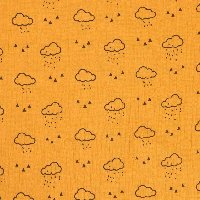 Tissu double gaze de coton Nuages noirs sur fond Moutarde - Par 10 cm