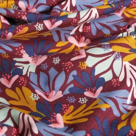 Tissu Jersey Coton Arty Feuillages ocre rose et bleus sur fond Lie de vin - Par 10 cm